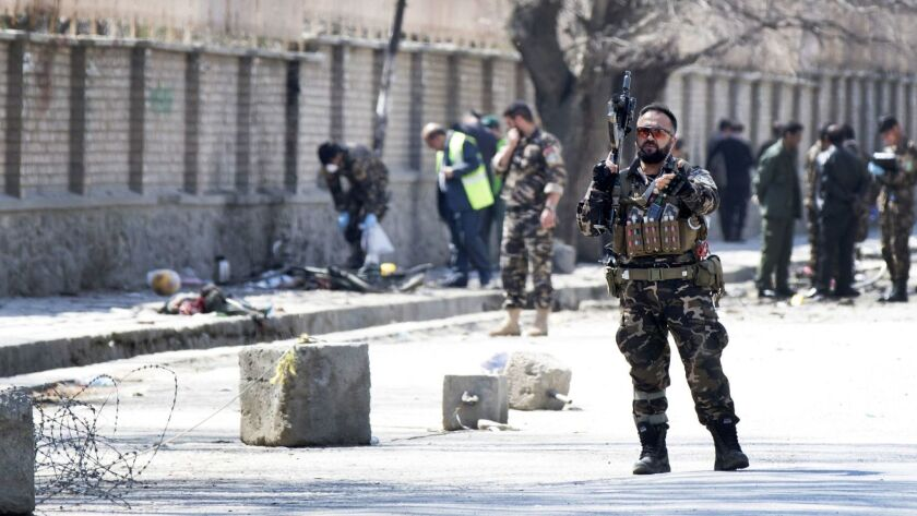 Security officials inspect the scene of a suicide bomb blast on March 21, 2018, that targeted a shrine visited by Shiite Muslims in Kabul, Afghanistan, as the country observes Nowruz, the Persian New Year.