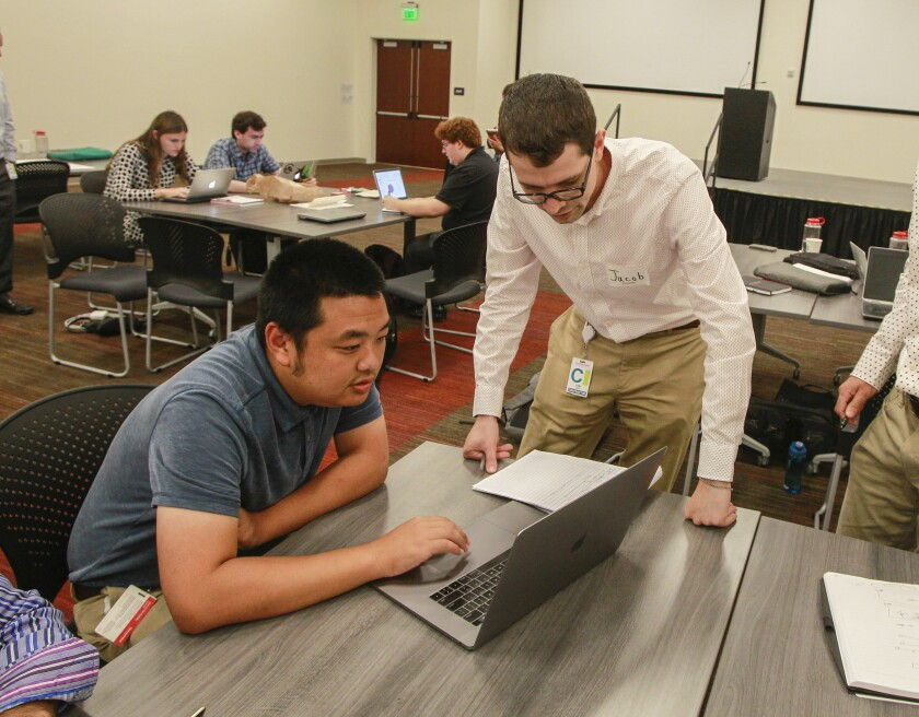 Ted Chang, left, and Jacob Rachal, right, work on a project at Thermo Fisher Scientific during a hiring training program to promote neurodiversity in the workplace on Aug. 16 in Carlsbad. Chidester is part of a group of adults with autism who are hoping to get jobs at Thermo Fisher.
