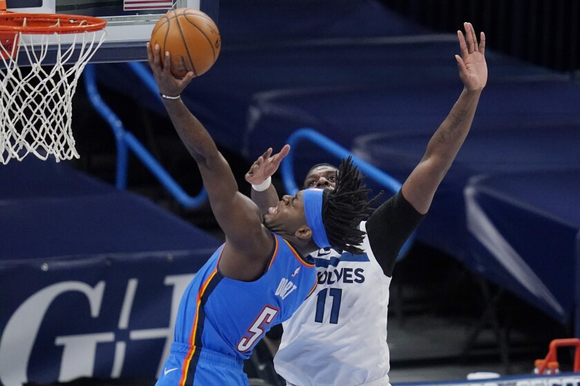 Oklahoma City Thunder forward Luguentz Dort (5) shoots in front of Minnesota Timberwolves center Naz Reid (11) in the second half of an NBA basketball game, Saturday Feb. 6, 2021, in Oklahoma City. (AP Photo/Sue Ogrocki)