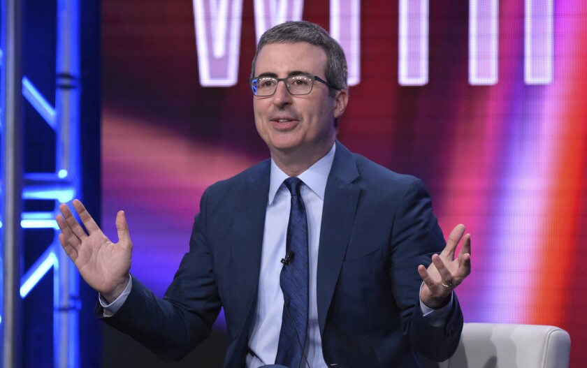John Oliver seated before a colorful background.