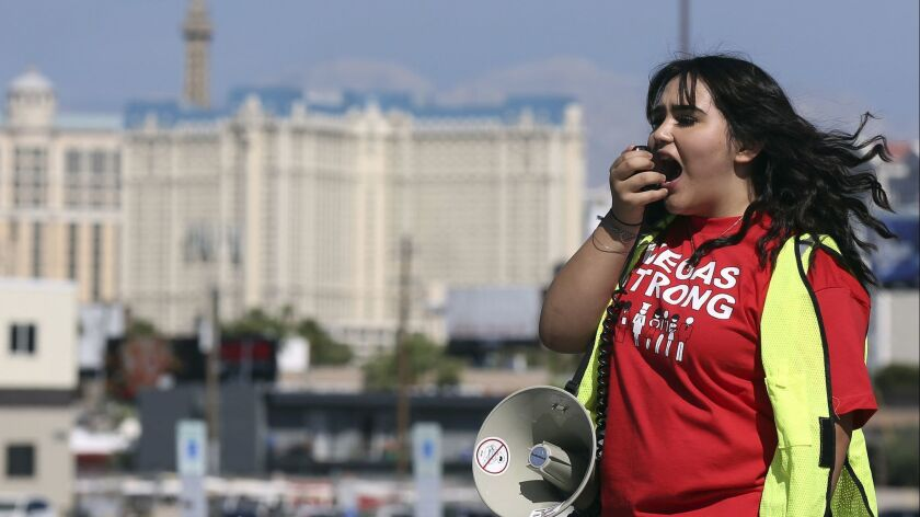 Jenifer Murias yells into a megaphone as Culinary Union members line up to vote on whether to authorize a strike in Las Vegas.
