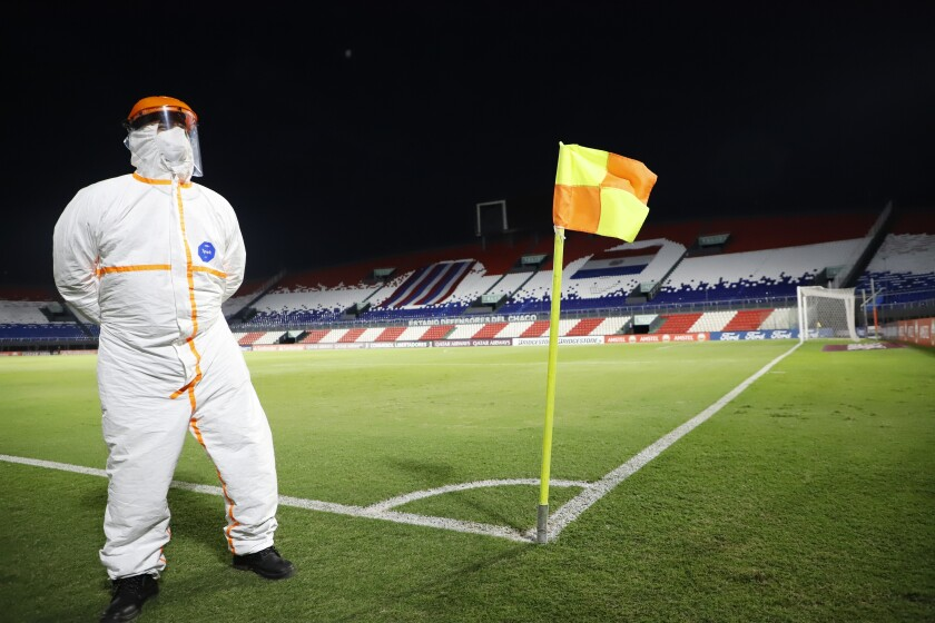"""A Conmebol worker stands guard on the pitch at the """"Defensores del Chaco"""" Stadium before the start of a Copa Libertadores soccer match between Brazil's Gremio and Ecuador's Independiente del Valle, in Asuncion, Paraguay, Friday, April 9, 2021. (Natalia Aguilar/Pool via AP)"""