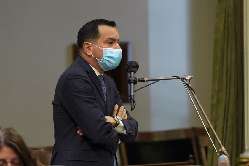 A man speaks at podium while wearing a mask