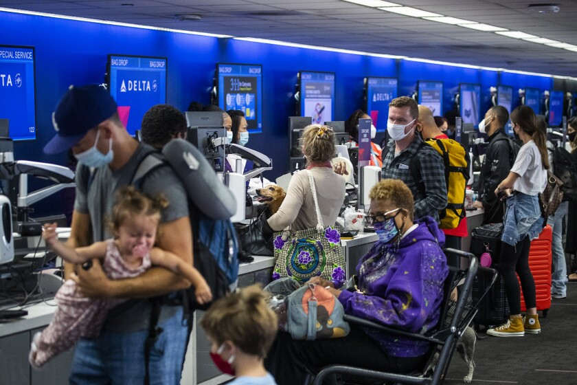 A crowd of Memorial Day weekend travelers check in for flights at LAX at Delta Airlines, Terminal 2 Friday, May 28, 2021.