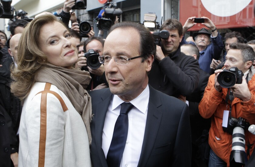 In 2012, presidential candidate Francois Hollande and companion Valerie Trierweiler leave after voting in Tulle, central France.