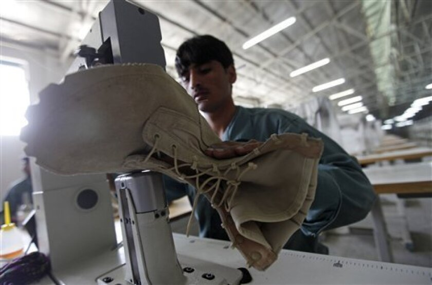 In this photo taken on Sept. 8, 2010, an Afghan man works on part of an army boot at the Kabul Milli boot factory in Kabul, Afghanistan. Contracting with the U.S. military to make boots for Afghan soldiers and police doubled the work force at the factory and guaranteed steady business for months, and possibly years, to come. (AP Photo/ Mustafa Quraishi)