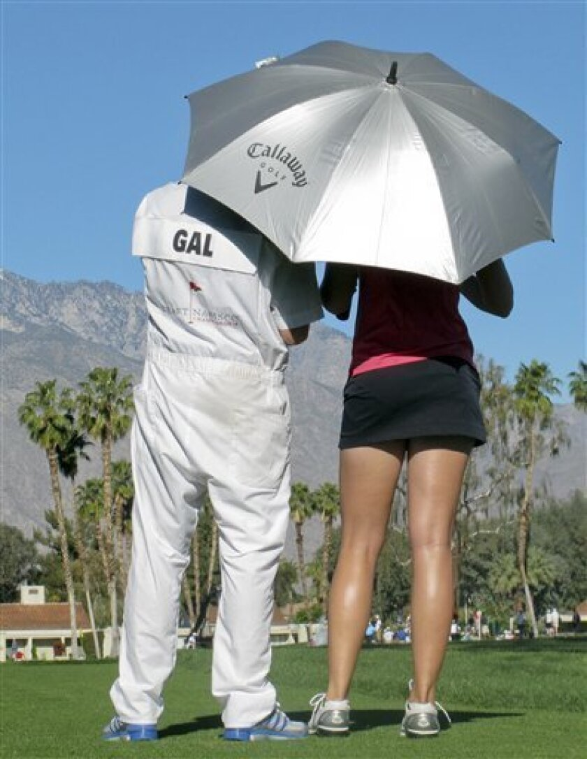 Sandra Gal of Germany, talks with her caddie on the fifth hole during the first round of the LPGA Kraft Nabisco Championship golf tournament  in Rancho Mirage, Calif., Thursday, March 31, 2011. (AP Photo/Chris Carlson)
