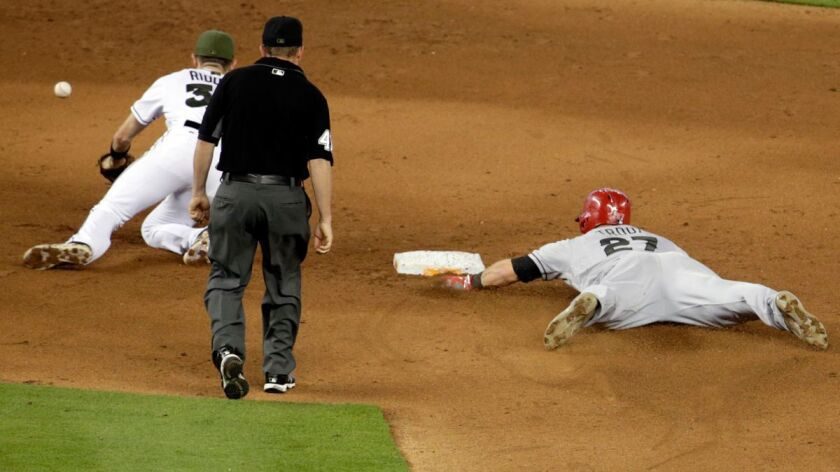 The Angels' Mike Trout (27) steals second base as the ball gets away from Miami Marlins shortstop J.