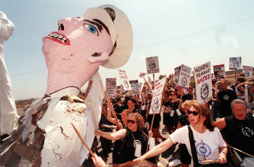 Demonstrators beat the effigy of a Navy flier while protesting sexism in the military in front of then-Naval Air Station Miramar in 1992, a year after the Tailhook scandal.