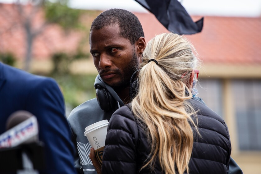 Jesse Evans embraces community member and friend Amie Zamudio during a news conference in May about his arrest in La Jolla.