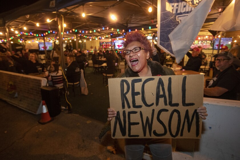 A woman yells outside a bar patio with a cardboard sign that says Recall Newsom