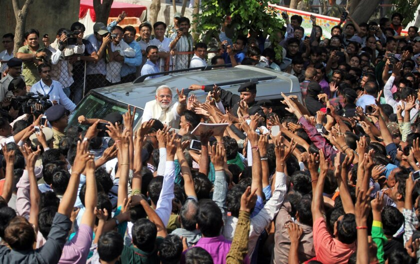 India's main opposition Bharatiya Janata Party's prime ministerial candidate Narendra Modi displays the victory symbol to supporters after casting his vote in Ahmadabad, India, Wednesday, April 30, 2014. Modi's carefully crafted and well-financed campaign presents him as a can-do politician who has turned his home state of Gujarat into a haven for business and industry, and has pledged to bolster India's growth. His image has been tainted by the 2002 sectarian violence that ripped through his home state, killing nearly 1,000 Muslims. Modi, who has been chief minister of the state since 2001, is widely seen as doing little to stop the violence, and his fiercest critics have accused him of organizing the bloodshed. (AP Photo/Ajit Solanki)