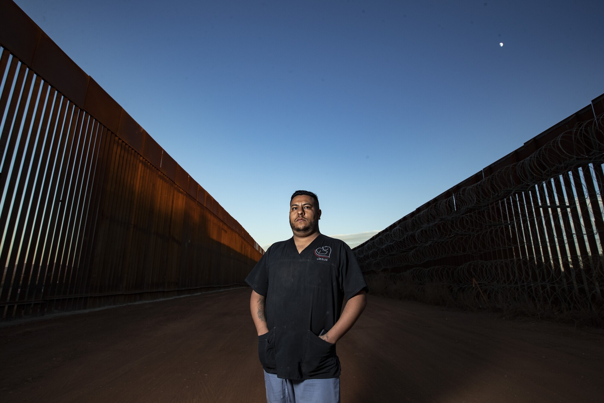 Veterinary assistant Jesus Tarazon stands for a portrait between the new border wall and the old wall.