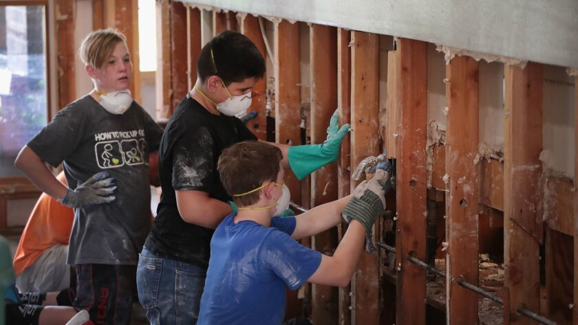Young helpers strip a wall down to its studs in a flood-damaged home after Harvey moved through Hous