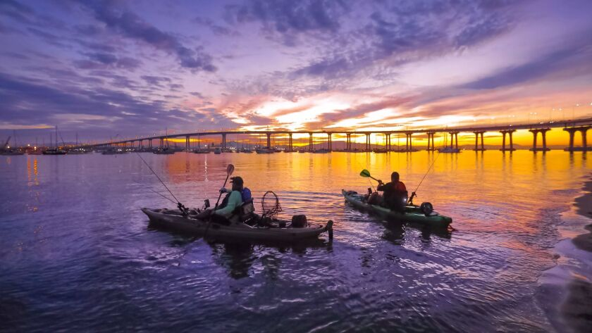 Against a backdrop of a dramatic morning sky, Phil Jones, left, and Gary Zalusky, right, head into San Diego Bay for a morning of fishing from the launch area at Tidelands Park in Coronado.