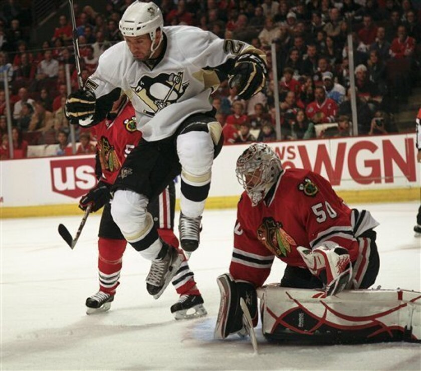 The Pittsburgh Penguins Max Talbot jumps to avoid a shot on goalie Corey Crawford of the Chicago Blackhawks during the first period of a hockey game Friday October 1, 2010. (AP Photo/Charles Cherney)