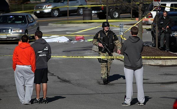 Police secure the scene where a gunman killed a campus police officer and one other person after a traffic stop Thursday.