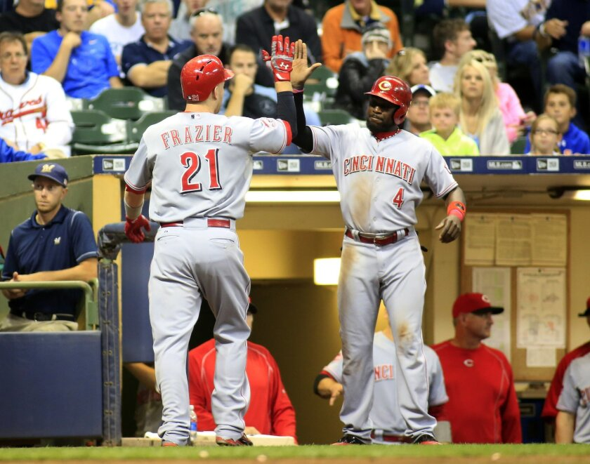 Cincinnati Reds' Todd Frazier, left, is congratulated on his two-run home run against the Milwaukee Brewers by Cincinnati Reds' Brandon Phillips during the sixth inning of a baseball game Saturday, Sept. 19, 2015, in Milwaukee. (AP Photo/Darren Hauck)