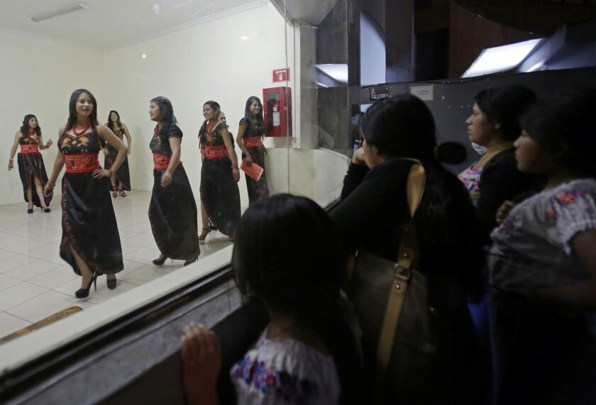 In this Friday, May 22, 2015 photo, beauty contestants rehearse the presentation parade for the Miss Indigenous Ecuador beauty contest, in a waiting area backstage at the Casa de la Cultura theater, in Quito, Ecuador. Contestants for the beauty contest have to belong to one of the country's many Indian groups and speak a native language. (AP Photo/Dolores Ochoa)