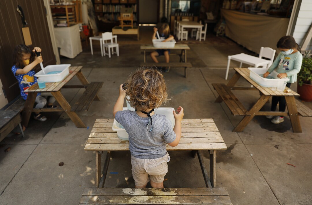 Children do activities at separate tables at Voyages Preschool.