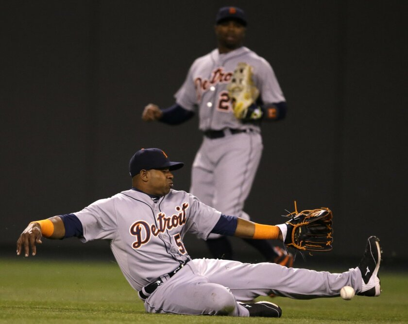 Detroit Tigers left fielder Yoenis Cespedes (52) misses a fly ball hit by Kansas City Royals' Omar Infante during the seventh inning of a baseball game at Kauffman Stadium in Kansas City, Mo., Thursday, April 30, 2015. Infante singled on the play. Detroit Tigers center fielder Rajai Davis (20) back