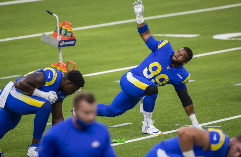 The Rams' Aaron Donald (99) stretches before a team scrimmage on SoFi Stadium.