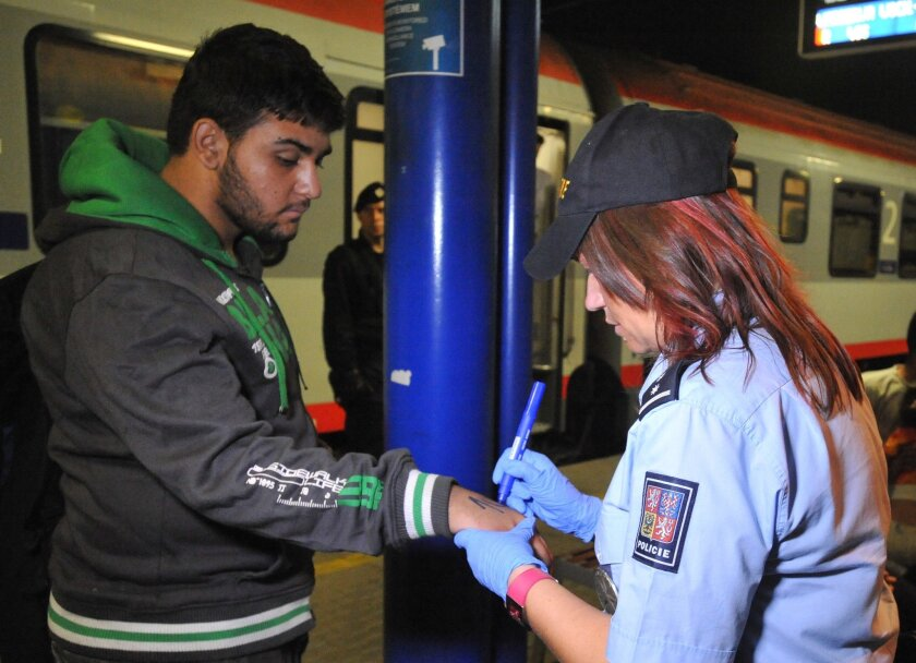 A Czech police officer marks a refugee with a number at the railway station in Breclav. (Igor Zehl / Associated Press)