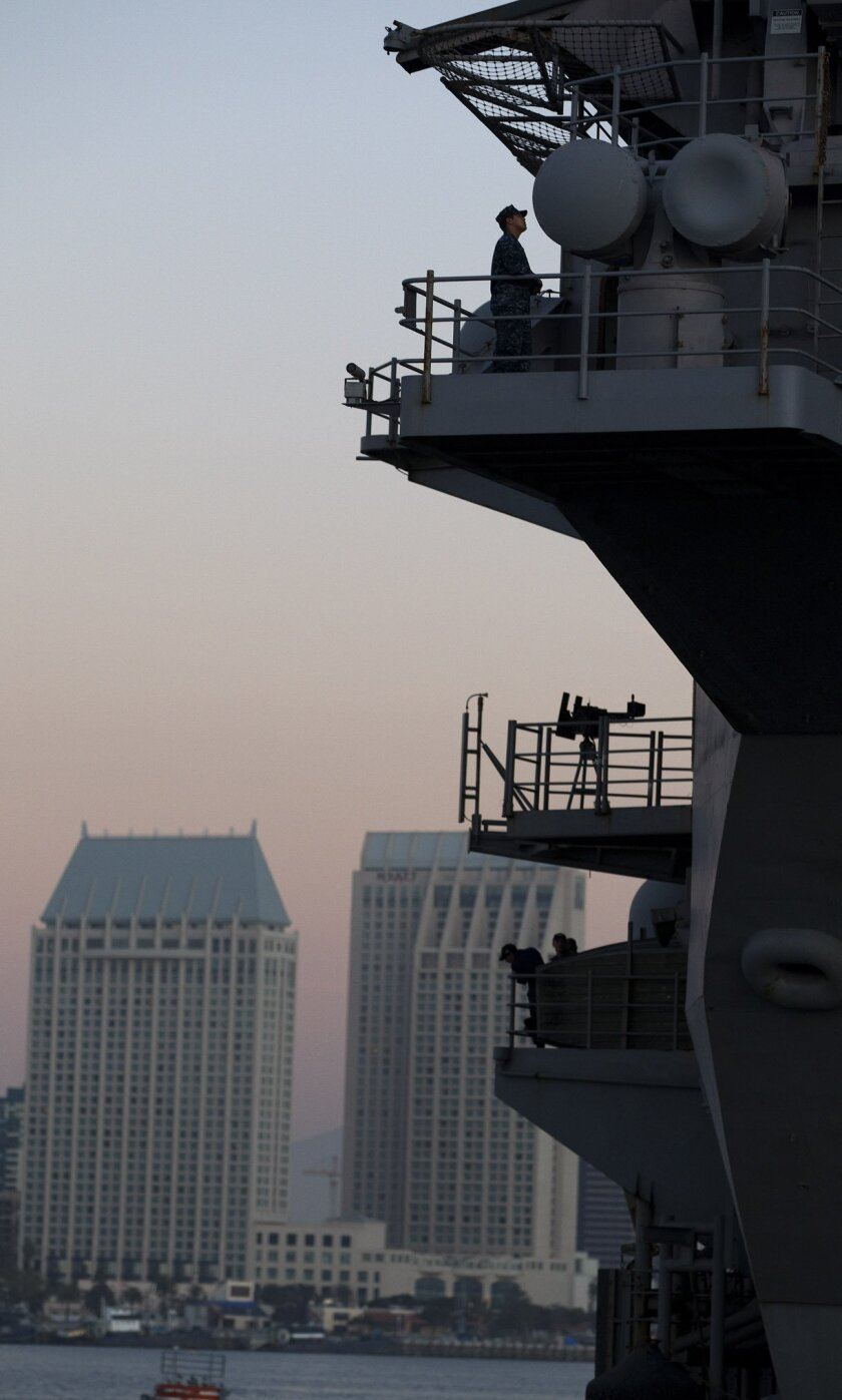 Crew members of the USS Ronald Reagan watches their ship departs San Diego for its trip to Washington state for its year-long overall.
