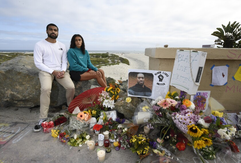 David Grant-Williams and Ruthie Grant-Williams pose next to a memorial for George Floyd on Ocean Blvd. in Coronado.
