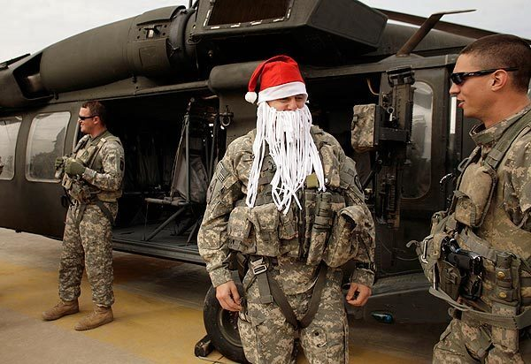 After flying in a Blackhawk helicopter, U.S. Army Chief Warrant Officer Derrick Nunley, 27, from De Soto, Kan., celebrates Christmas by wearing a Santa Claus hat and a beard made out of a shredded T-shirt at Camp Victory, the U.S. military headquarters on the western edge of Baghdad.