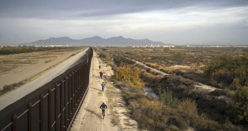 En esta imagen de enero de 2018 difundida por Fin and Fur Films, un grupo de cineastas y fotógrafos de vida silvestre recorren en bicicleta un camino aledaño al muro fronterizo al sur del Parque Nacional Big Bend, Texas. (Fin and Fur Films via AP)