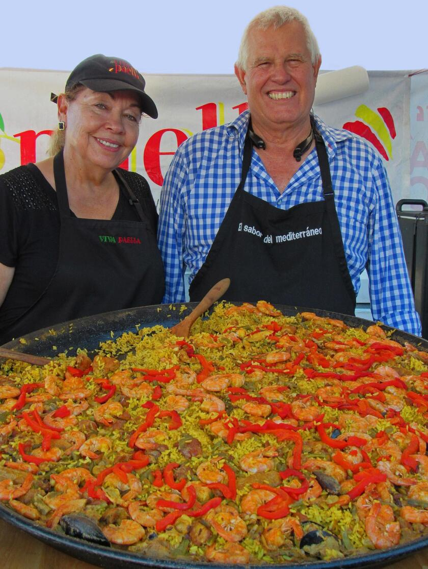 Elda and Antonio Delgado pose with the colorful homemade paella they sell each Wednesday at the OB Farmers Market.