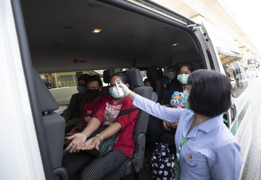 Health officer check temperature passenger in van at a health check point in Bangkok, Thailand, Thursday, March 26, 2020. It is the first day of month long state of emergency enforced in Thailand to allow its government to impose stricter measures to control the coronavirus that has infected hundreds of people in the Southeast Asian country. (AP Photo/Sakchai Lalit)
