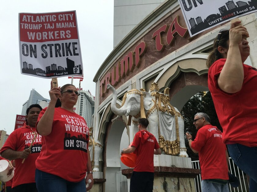 Striking union members walk a picket line outside the Trump Taj Mahal casino in Atlantic City, N.J. on Friday July 1, 2016. Local 54 of the Unite-HERE union went on strike against the casino, which is owned by billionaire investor Carl Icahn.  (Brian Ianieri/The Press of Atlantic City via AP) MANDA