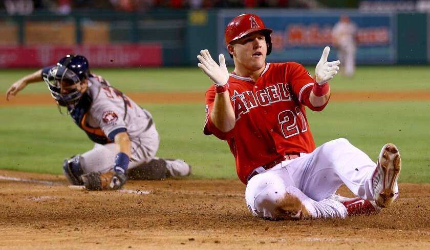 Angels center fielder Mike Trout celebrates as he slides safely past Astros catcher Jason Castro during a game at Angel Stadium.