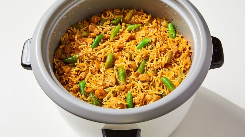 Tahdig rice with chicken and green beans in a Persian rice cooker