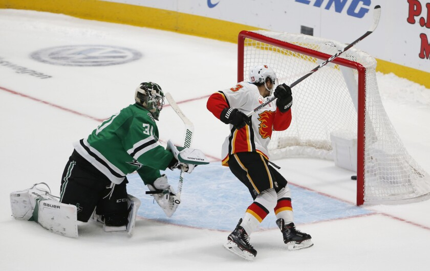 Calgary Flames left wing Johnny Gaudreau (13) gets the puck past Dallas Stars goaltender Ben Bishop (30) to score during the shootout in an NHL hockey game in Dallas, Thursday, Oct. 10, 2019. Calgary won 3-2. (AP Photo/Michael Ainsworth)