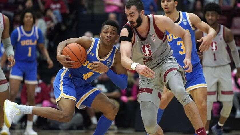 Stanford center Josh Sharma (20) battles for the ball against UCLA guard Jaylen Hands (4) during the