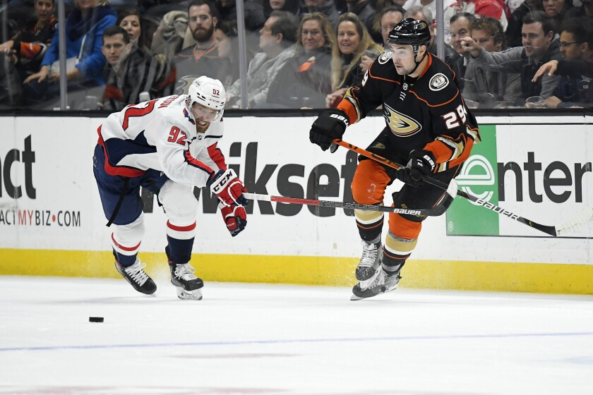 Washington Capitals center Evgeny Kuznetsov, left, and Ducks center Devin Shore compete for the puck during the second period on Friday at Honda Center.
