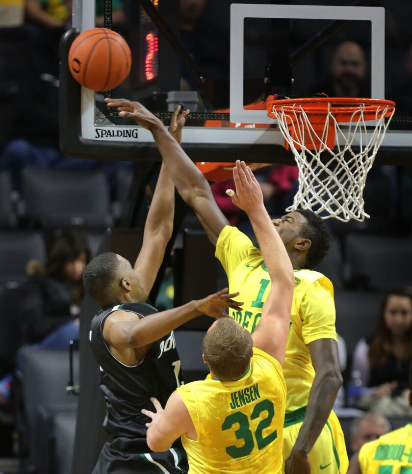 Portland State's Braxton Tucker, left, has his shot seated away by Oregon's Jordan Bell as he and teammate Tim Jensen, center, defend under the Viking basket during the first half of their NCAA basketball game in Eugene, Oregon, Sunday Nov. 30, 2014. (AP Photo/The Register-Guard, Chris Pietsch)