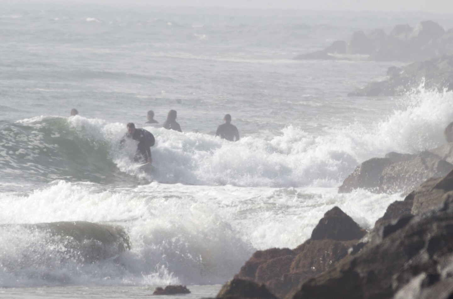 San Diego Surfers got a chance to surf the Mission Bay channel on Wednesday as the large swell was hitting the channel just right to give them tricky waves to ride.