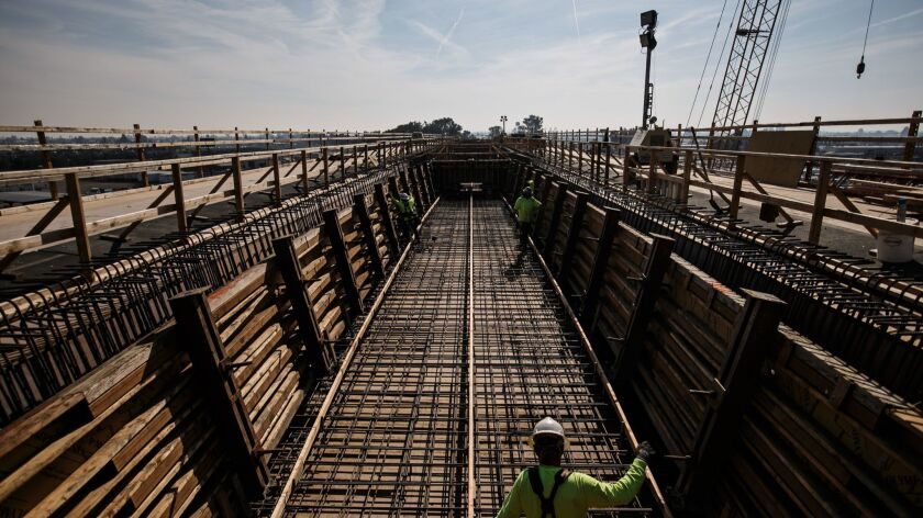Construction workers at a 3,700-foot viaduct built to extend over State Route 99 in Fresno County in 2017.