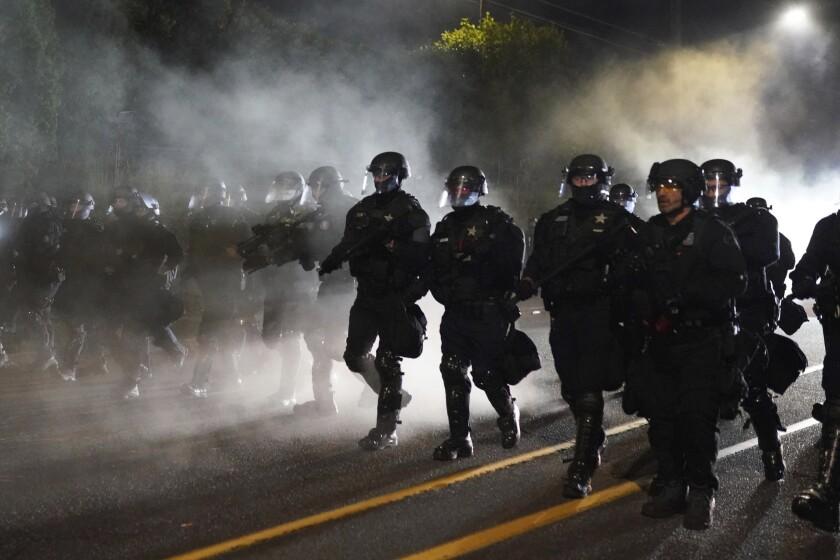 Portland police officers walk through the Laurelhurst neighborhood