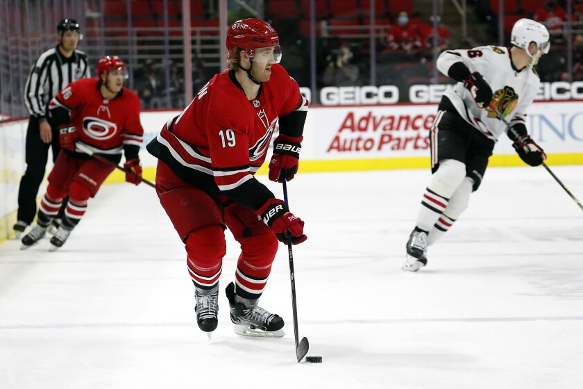 FILE - In this May 6, 2021, file photo, Carolina Hurricanes' Dougie Hamilton (19) skates with the puck against the Chicago Blackhawks during the third period of an NHL hockey game in Raleigh, N.C. The Devils agreed to term with Hamilton on a $63 million, seven-year contract. It's the most lucrative deal completed on the first day of NHL free agency. (AP Photo/Karl B DeBlaker, File)
