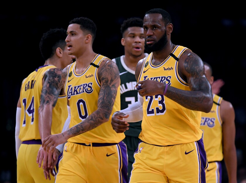 The Lakers' LeBron James (23) and Kyle Kuzma (0) react after a James score at Staples Center on March 6.