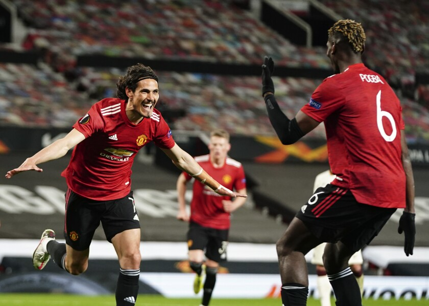 Manchester United's Edinson Cavani, left, celebrates after scoring his side's third goal during the Europa League semi final, first leg soccer match between Manchester United and Roma at Old Trafford in Manchester, England, Thursday, April 29, 2021. (AP Photo/Jon Super)