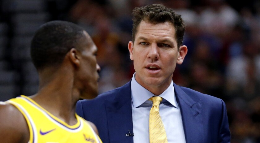 Lakers coach Luke Walton speaks with guard Rajon Rondo during a game on March 27.