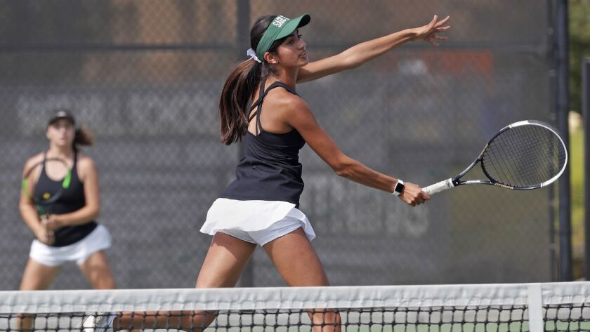 Sage Hill School's Karina Grover, center, scores at the net as partner Miranda deBruyne, left, looks on during a No. 1 doubles set against Mater Dei in a nonleague girls' tennis match on Tuesday.