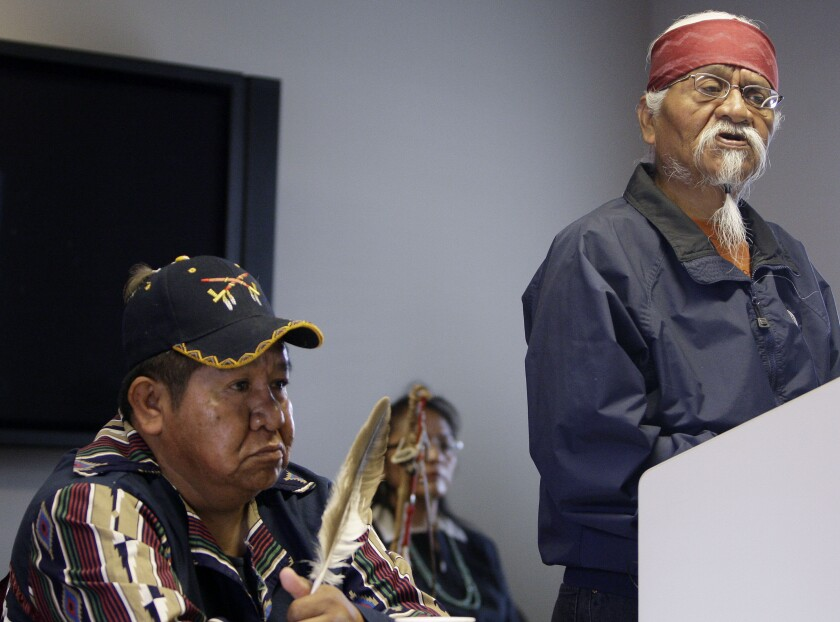 FILE — In this April 21, 2020 file photo Arizona Havasupai Indian tribe member, elder, and spiritual leader, Rex Tilousi, right, speaks during a news conference in Phoenix, as tribe member Dennie Wescogame listens. Tilousi, 73, died last week of natural causes with his family by his side. Services for Tilousi begin Friday with a traditional wake at the family's home in the village of Supai. (AP Photo/Ross D. Franklin, File)