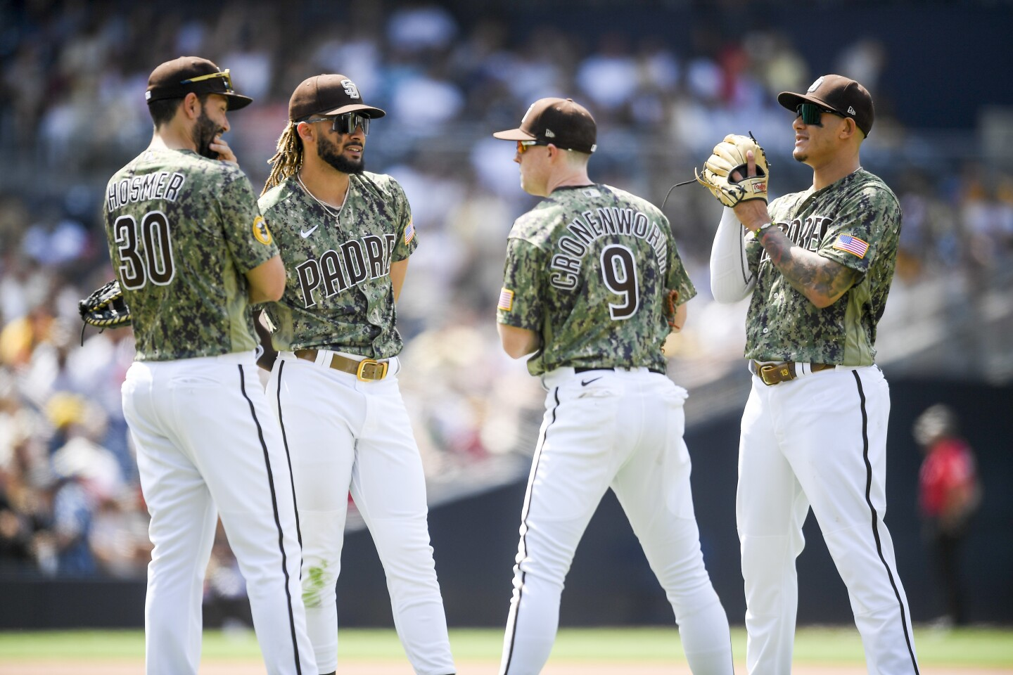SAN DIEGO, CA - JULY 11: Eric Hosmer #30, Fernando Tatis Jr. #23, Jake Cronenworth #9 and Manny Machado #13 of the San Diego Padres talk on the field during the seventh inning of a baseball game agains the Colorado Rockies at Petco Park on July 11, 2021 in San Diego, California. (Photo by Denis Poroy/Getty Images)